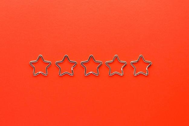 Vijf glanzende metalen split-sleutelhangers in de vorm van een ster voor sleutelhangers. verchroomde sleutelhangersluiting op rode achtergrond.