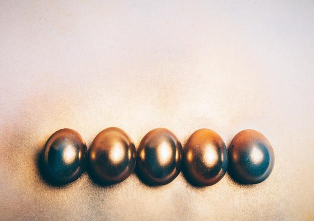 Vijf gouden eieren die op de vloer leggen.