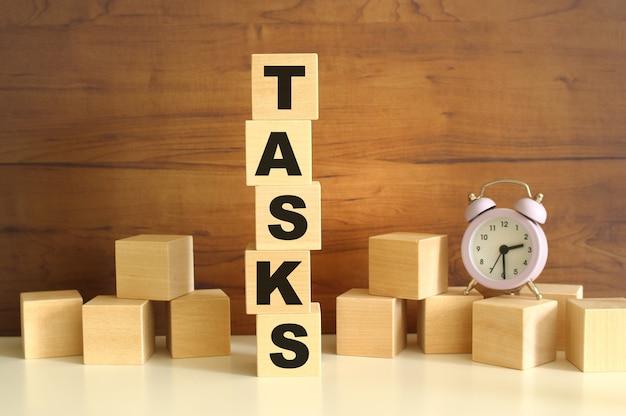 Vijf houten kubussen verticaal gestapeld op een bruine achtergrond vormen het woord taken.