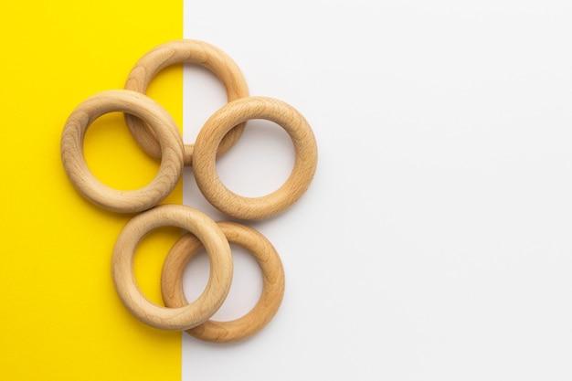 Vijf houten ringen op wit-gele achtergrond. babybijtring van natuurlijk hout. milieuvriendelijk kinderspeelgoed.