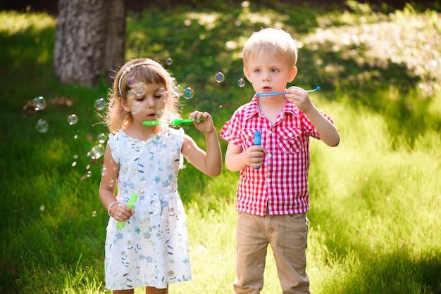 Vijf jaar oud kaukasisch kindmeisje en jongens blazende zeepbels