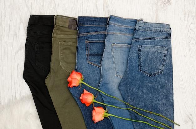 Vijf jeans in verschillende kleuren, oranje rozen.