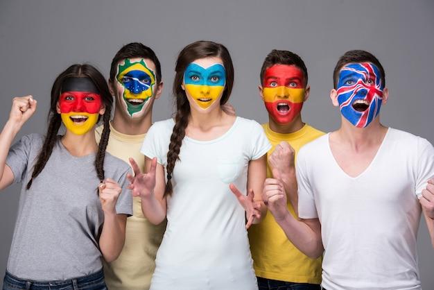 Vijf jonge mensen met nationale vlaggen geschilderd op de gezichten.