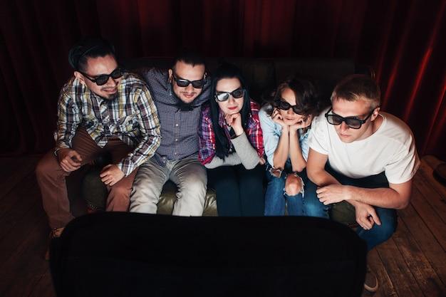 Vijf jonge vrienden met een 3d-bril zitten op de bank en kijken met aandacht naar de filmpremière op tv
