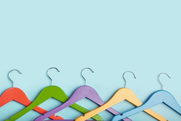 Vijf kinderhangers voor kleding in regenboogkleuren.