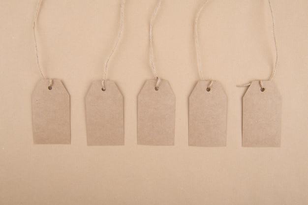 Vijf labels van gerecycled kraftpapier die aan een touw op kraftpapier hangen. plat leggen