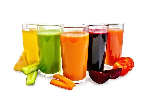 Vijf lange glazen met sap van wortel, komkommer, tomaat, rode biet en pompoen met groenteplakken die op witte achtergrond worden geïsoleerd