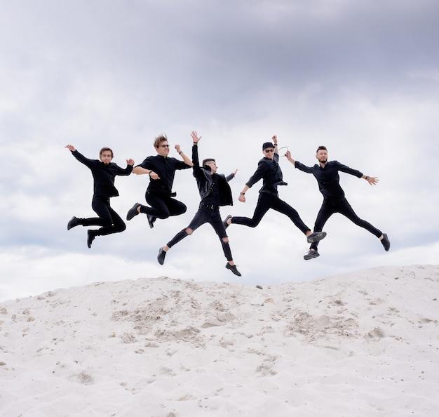 Vijf mannen gekleed in zwarte kleding springen in de lucht en poseren voor een fotoshoot op de zandheuvel op de hemelachtergrond