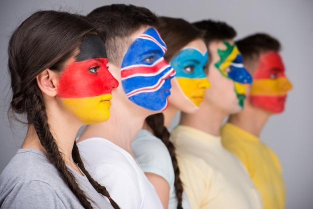 Vijf mensen met nationale vlaggen geschilderd op gezichten in profiel.