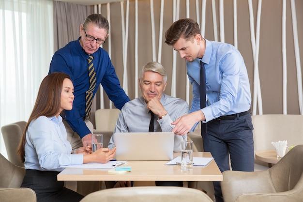 Vijf mensen uit het bedrijfsleven werken aan tafel in cafe