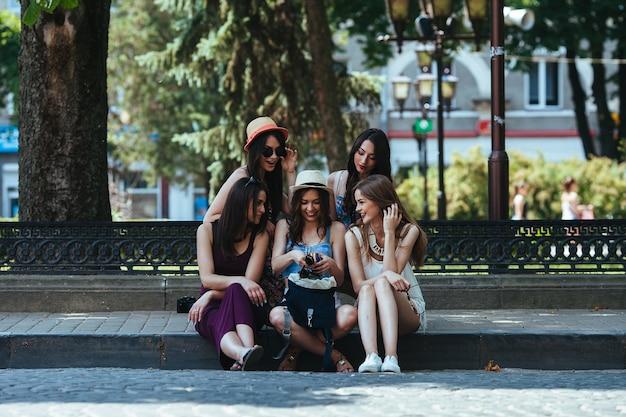 Vijf mooie jonge meisjes beschouwen de tas in het park