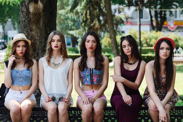 Vijf mooie jonge meisjes poseren in het park