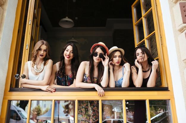Vijf mooie jonge vrouwen kijken uit het raam
