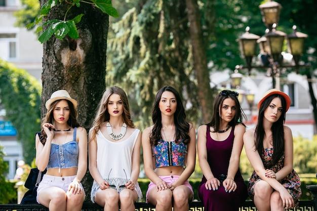Vijf mooie jonge vrouwen poseren in het park