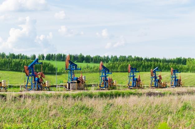 Vijf oliepompen onttrekken olie in het midden van groene velden