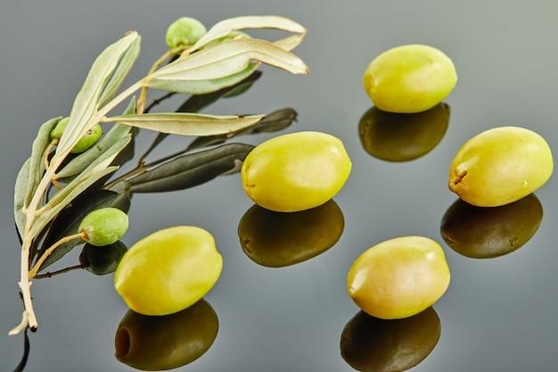 Vijf olijven met olijfboomtak met vruchten die op een grijze achtergrond liggen