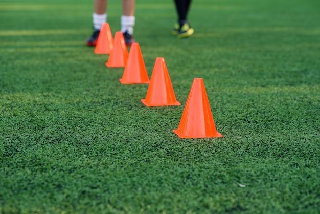 Vijf oranje trainingskegels op een kunstmatig voetbal of groen voetbalveld.