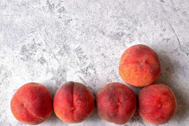 Vijf rijpe, sappige perziken, op een witte gevlekte achtergrond