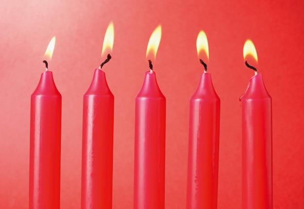 Vijf rode kaarsen op rood