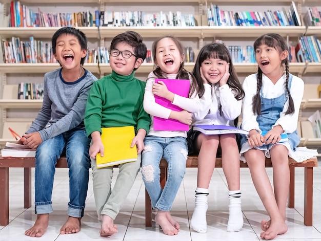 Vijf slimme kinderen zitten op een houten stoel, met een gelukkig gevoel, genieten met hun klas, op school.