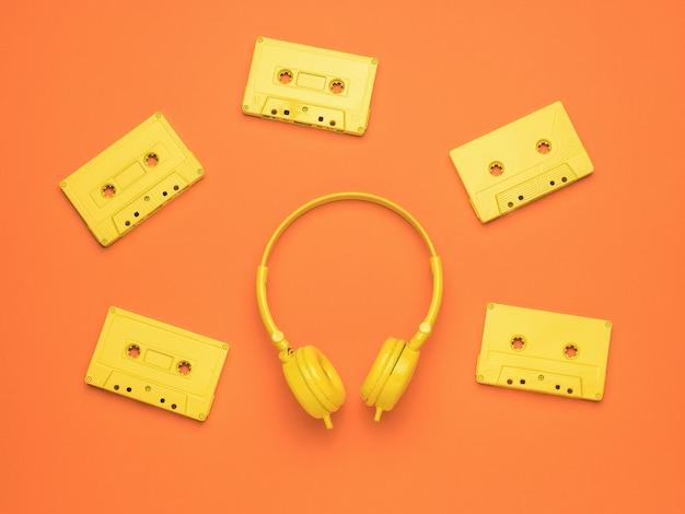 Vijf stijlvolle gele tapecassettes en gele koptelefoons op een oranje achtergrond. kleur trend. vintage apparatuur om naar muziek te luisteren. plat leggen.