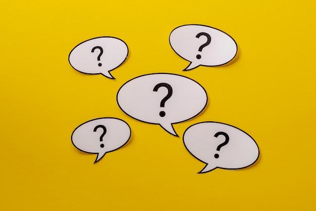 Vijf tekstballonnen met vraagtekens op een felgele achtergrond
