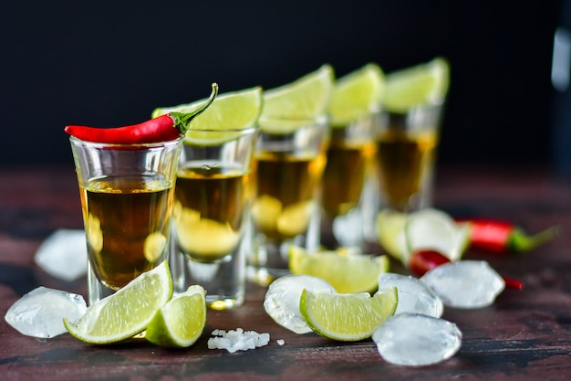 Vijf tequila shots met snacks limoen en pistache, zout en chili peper voor decoratie, wodka, whisky, rum