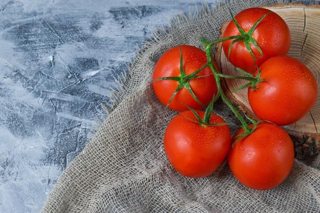 Vijf tomaten liggen op een houten standaard en een katoenen doek.