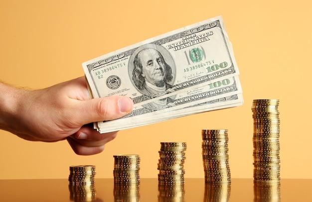 Vijf torens van gouden munten en hand met dollars