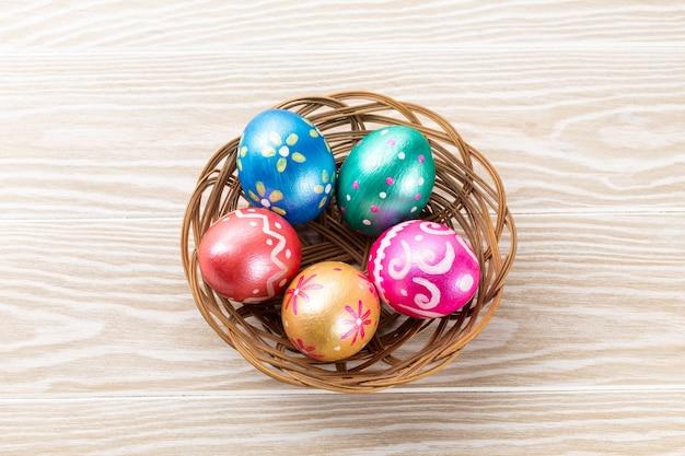 Vijf trendy gekleurde paaseieren diepblauw, groen, oranje, magenta en goud versierd in mand op wit