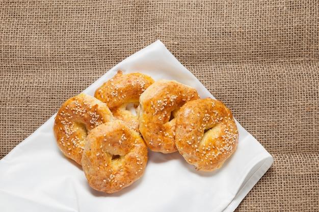 Vijf vers gebakken glutenvrije ringen op een witte theedoek.