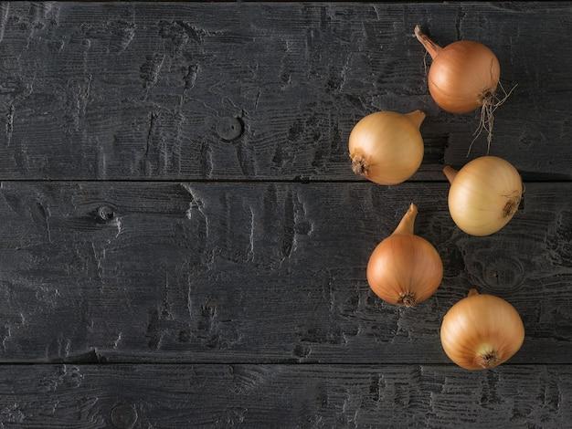 Vijf verse rijpe uien op een zwarte houten tafel.