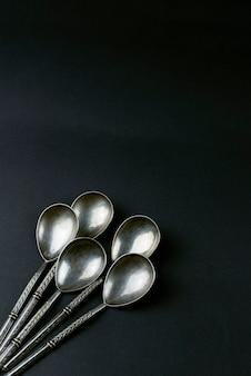 Vijf vintage zilveren theelepels op zwarte achtergrond