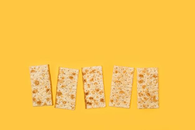 Vijf volkoren cracker koekjes op een gele achtergrond