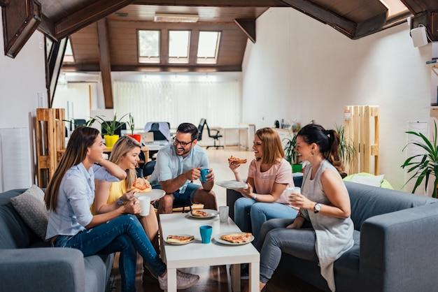 Vijf vrienden hebben plezier en eten pizza.