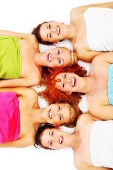 Vijf vriendinnen die plezier hebben in de spa op witte achtergrond