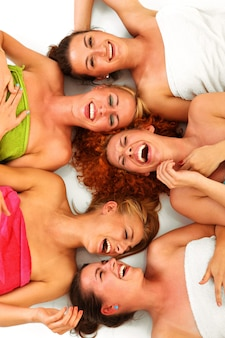 Vijf vriendinnen die plezier hebben in de spa over wit