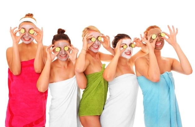 Vijf vriendinnen die plezier hebben met gezichtsmaskers op over wit