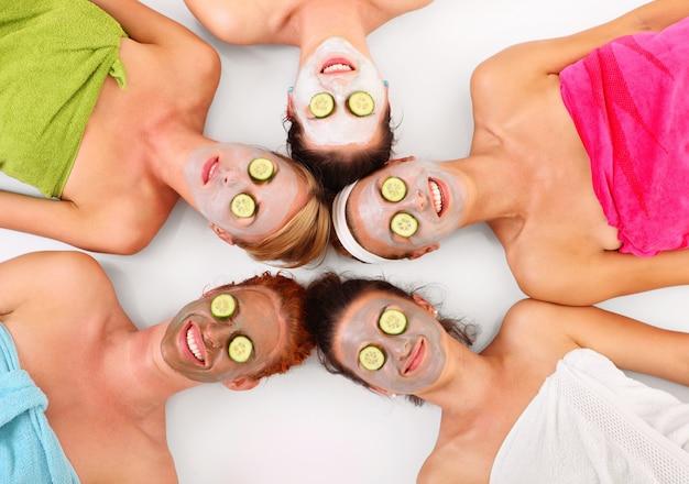 Vijf vriendinnen ontspannen met gezichtsmaskers op over wit