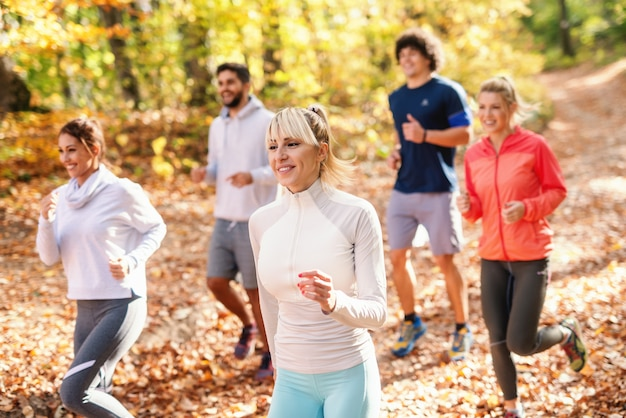 Vijf vrolijke lopers in sportkleding die in bos bij de herfstgeschiktheid in aardconcept lopen. zijaanzicht.