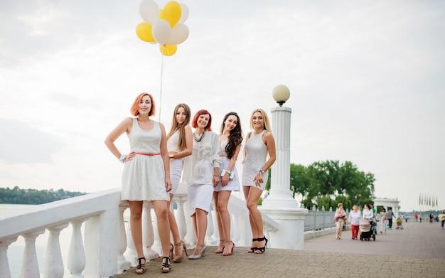 Vijf vrouwen met ballonnen bij de hand weared op witte jurken op vrijgezellenfeest tegen pier op meer.