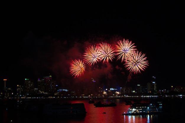 Vijf vuurwerk op strand en bezinningskleur op waterspiegel