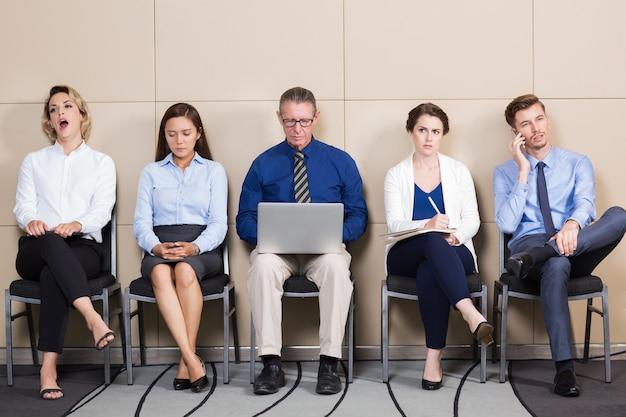 Vijf zakenmensen wachten op sollicitatiegesprek