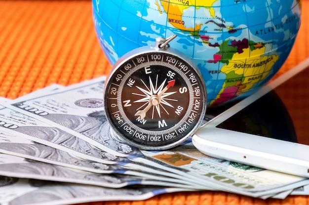 Vijfhonderd amerikaanse dollar bankbiljetten, kompas, bol van de planeet aarde