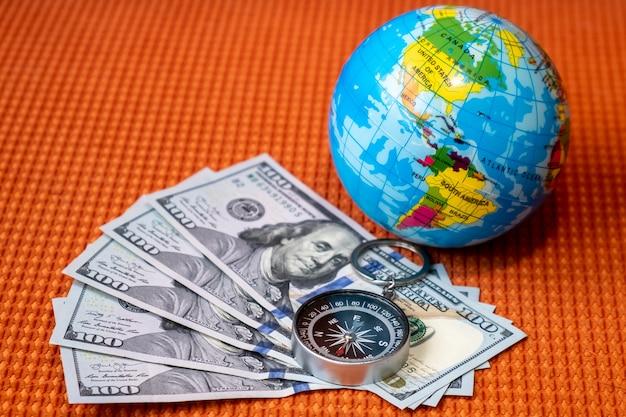 Vijfhonderd amerikaanse dollars, kompas, bol van de planeet aarde. reizen, toerisme, avonturen concept.