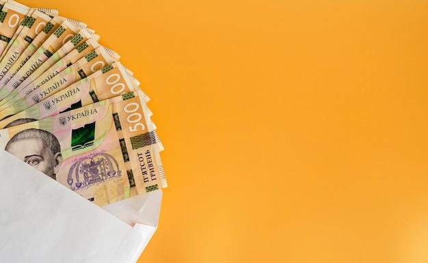 Vijfhonderd oekraïense hryvnia in een envelop op een oranje achtergrond 5
