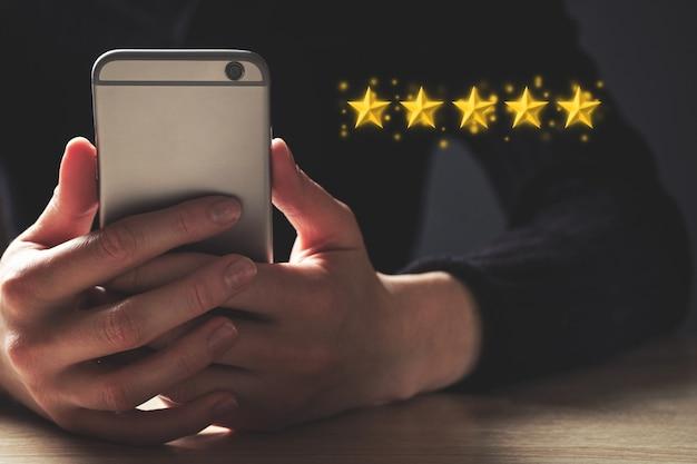 Vijfsterrenclassificatieconcept. de persoon gebruikt een smartphone voor feedback.