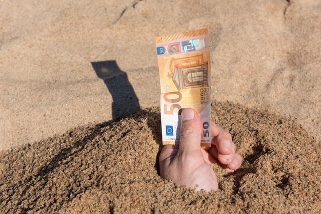 Vijftig euro in de hand van een man die uit het zand steekt