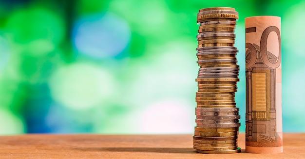 Vijftig euro rolde bill bankbiljet, met euromunten op groene wazig bokeh achtergrond.