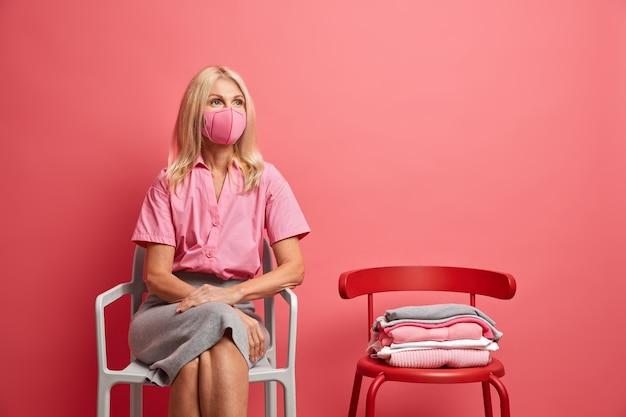 Vijftig jaar oude blonde vrouw draagt gezichtsmasker op zelfisolatie. quarantaine concept